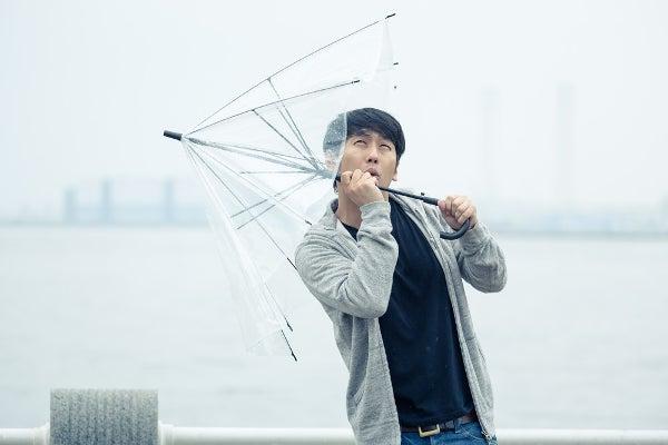 台風の時、傘を指すビジネスマン