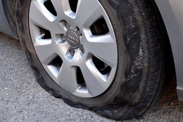駐車場でパンクしたタイヤ